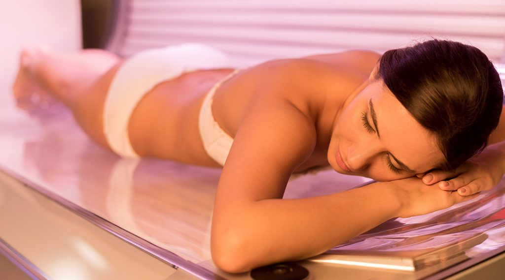 Woman laying in tanning bed